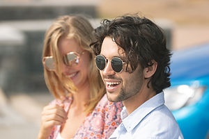couple with sun glasses standing on beach