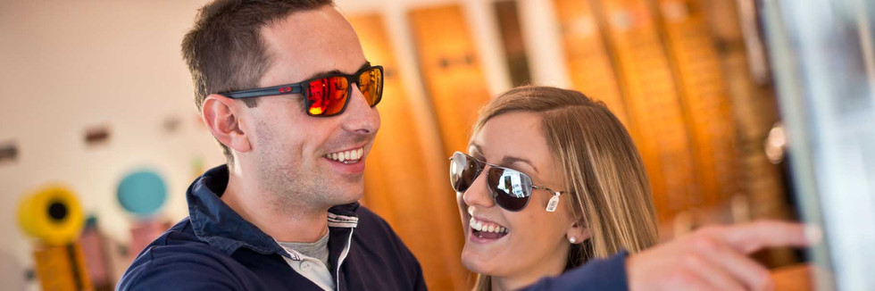 Couple trying on sunglasses at J. Oliver Radley Opticians