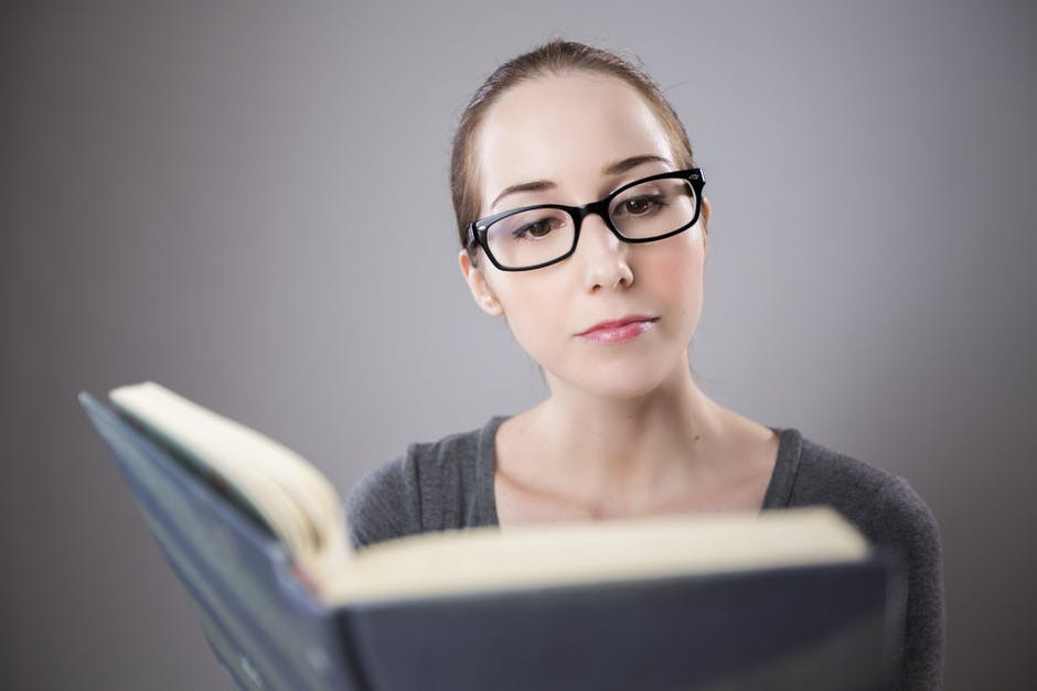 Women wearing glasses and reading a book