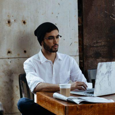 Man wearing glasses sat at his work desk.