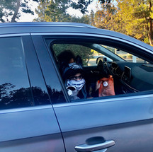 A masked BC kid shows off their goody bag after the Halloween 2020 Drive-BOO event