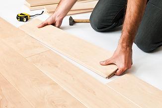Close up of man fitting hardwood floor panels.jpg