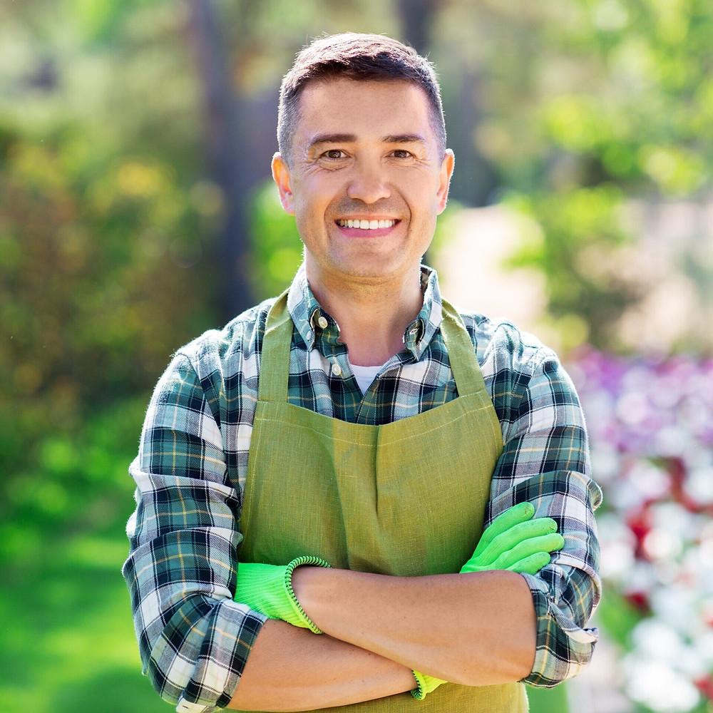 Man wearing apron and gardening gloves