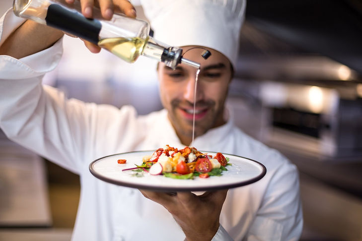 Chef drizzling oil on salad.jpg