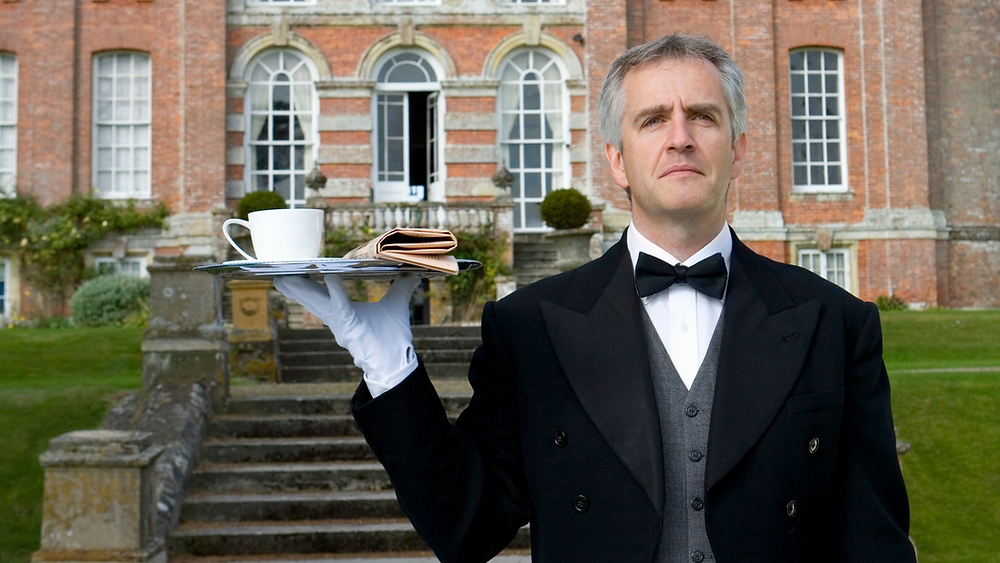 Butler holding cup and paper on tray in the gardens
