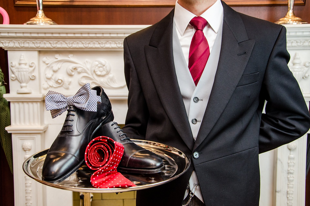 Butler carrying tray with shoes, bow tie and tie
