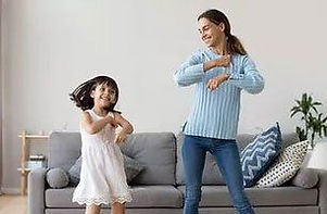 Nanny and child dancing in living room.j