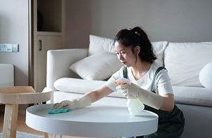 Housekeeper cleaning living room table.j