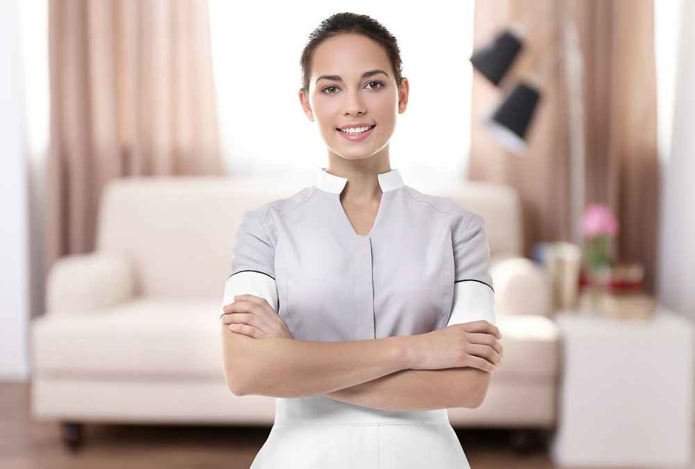 Housekeeper standing infront of sofa