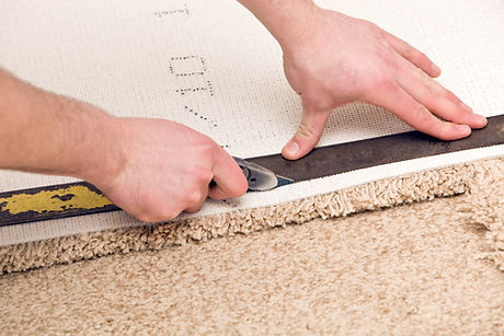 Cream carpet being cut to size.jpg