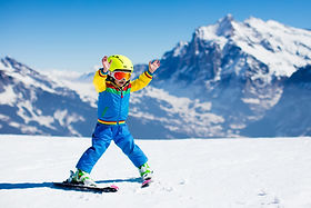 Child skiing in mountains. Active toddle