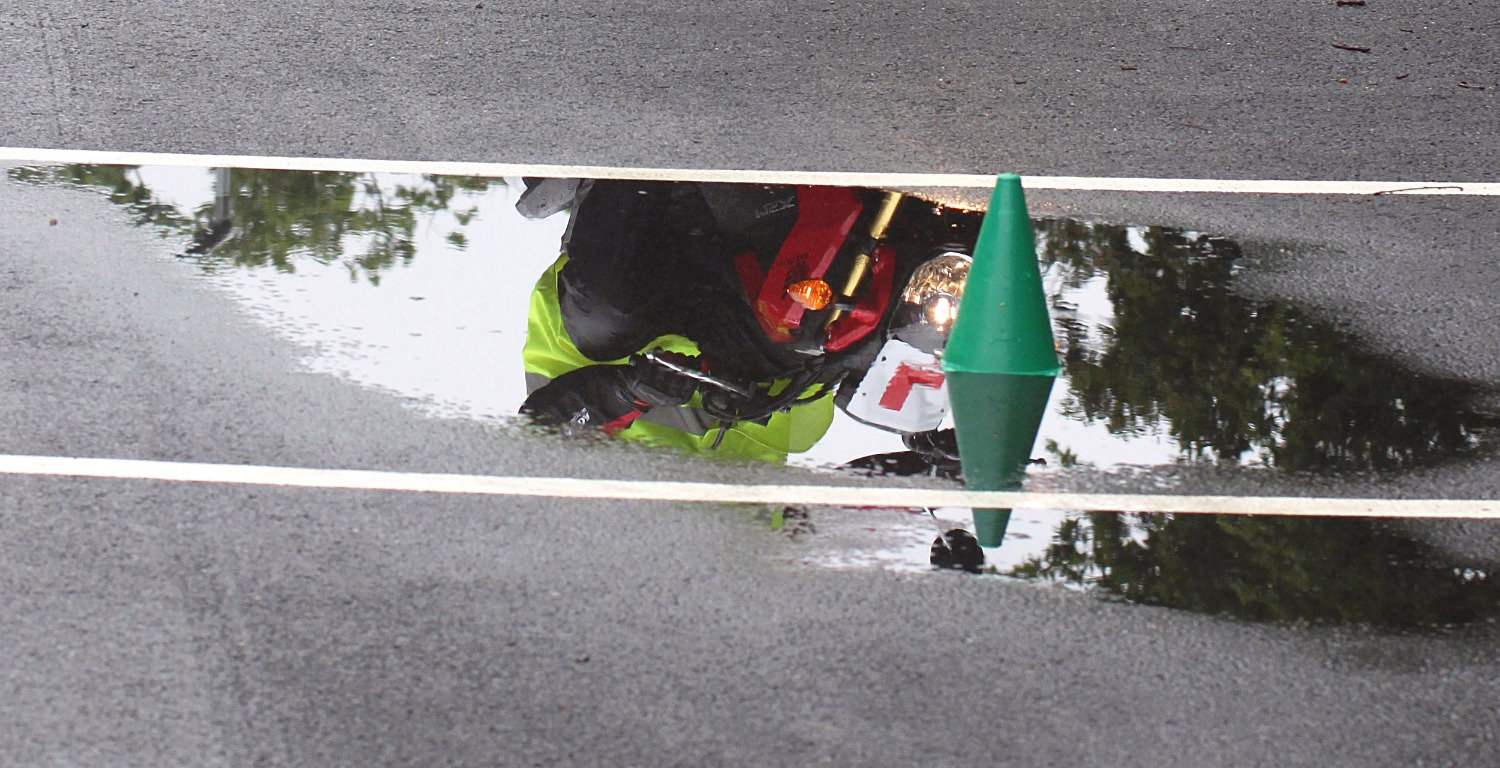 Learner motorcycle reflected in puddle