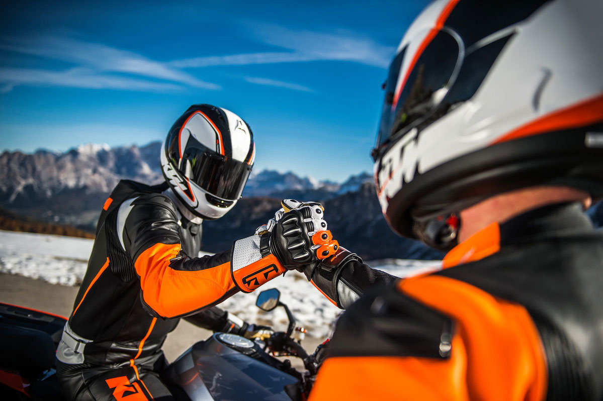 Motorcyclists gripping hands
