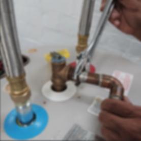 plumber fixing a broken water heate pipe