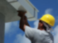 Hard hat construction man perfoming maintenance repairs and intallaton on gutter commercial or residential