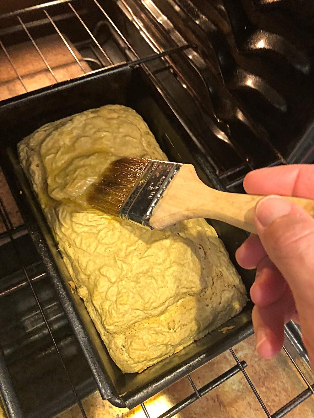Brushing ghee on top of loaf