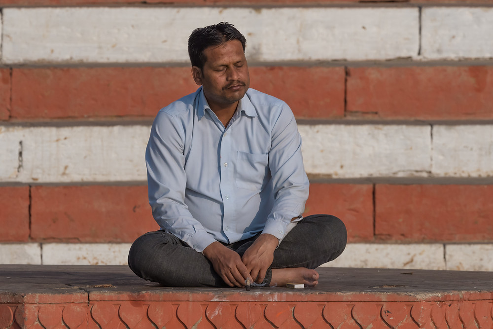Man meditating along the River Ganges, Varanasi, India