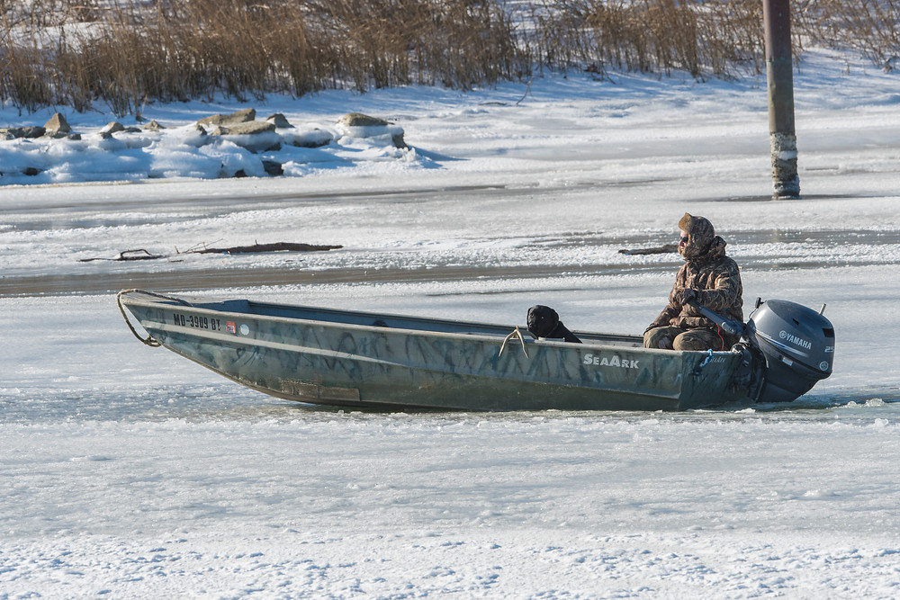 Duck hunter trying to motor through ice.