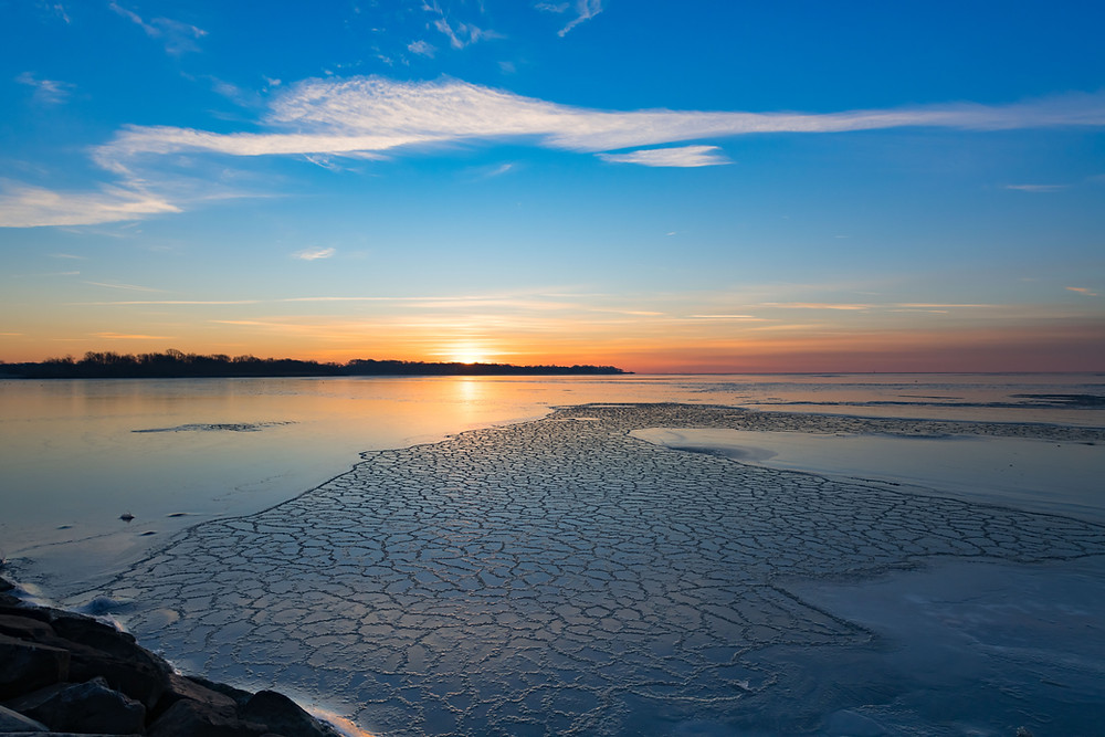 Sunrise over ice-covered South River. There is a line of white clouds in a bluish sky; crackled ice making a path towards the horizon.