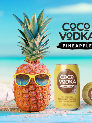 Coco vodka pineapple on beach with cans.