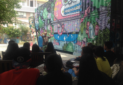 explaining aboout the mural process in front of a 3 story mural I did in HCMC.