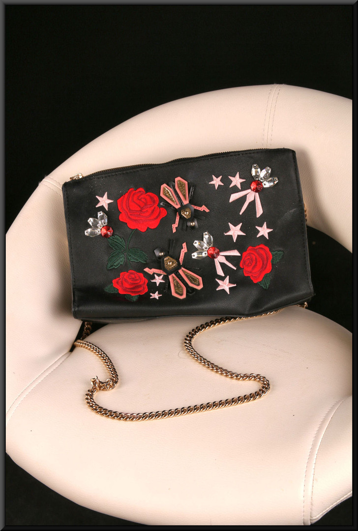 Black leather effect shoulder bag with roses and stars on the front and gold coloured heavy shoulder chain