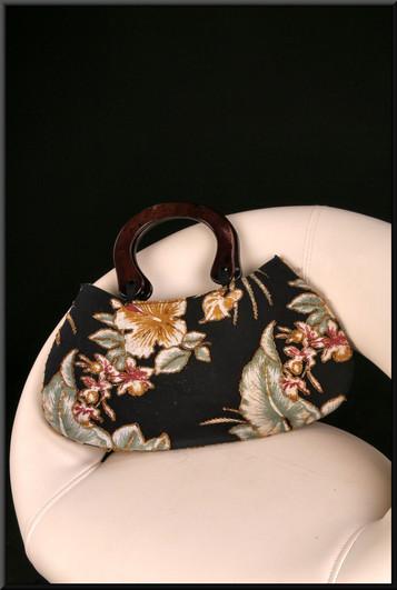 Black soft handbag with embroidered green leaf / pink petal pattern and horn effect handles