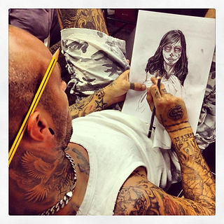 Marc in the Blood Brothers Tattoo Studio drawing a custom design