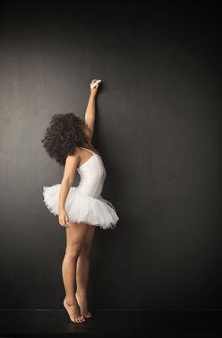 Young ballerina wiritting on blackboard.