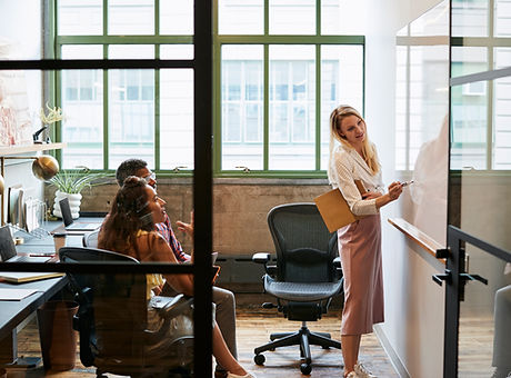 woman-at-whiteboard-in-team-meeting-seen