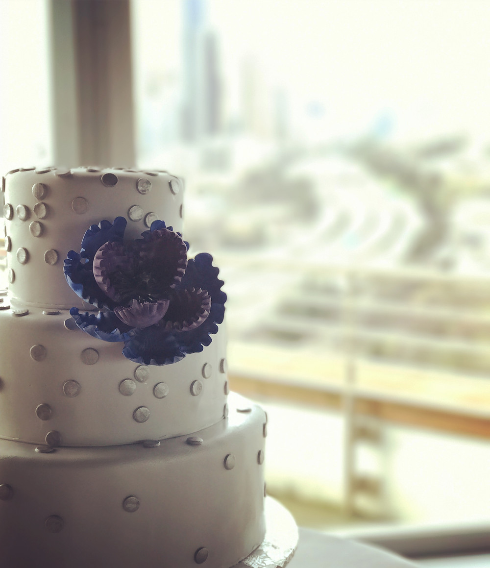 Tube Wedding Cake With Silver Dots and Purple Flowers
