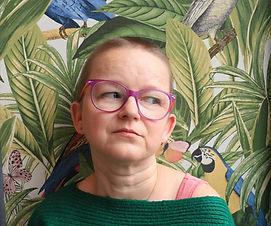 Zdjęcie przedstawia moją twarz na tle kolorowej i kwiecistej ściany. Zamiast w obiektyw patrzę w bok. Fot. Joanna Dryjańska
