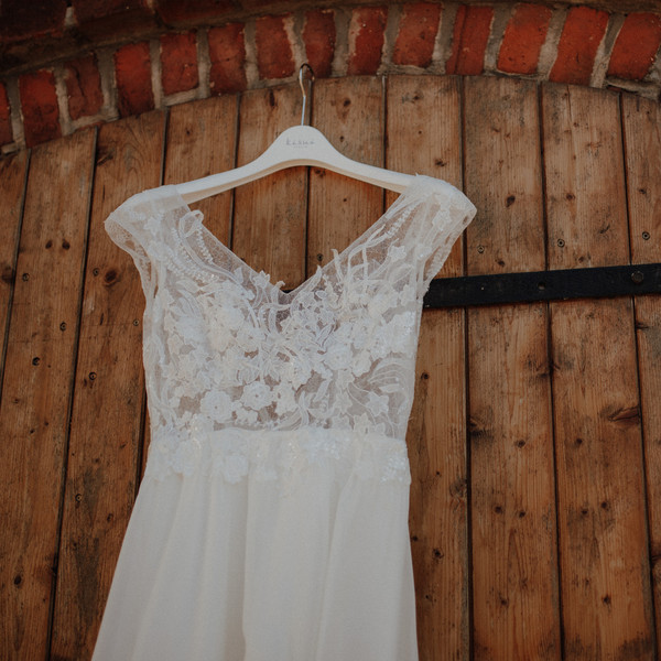 Brautkleid hängt an Holztür