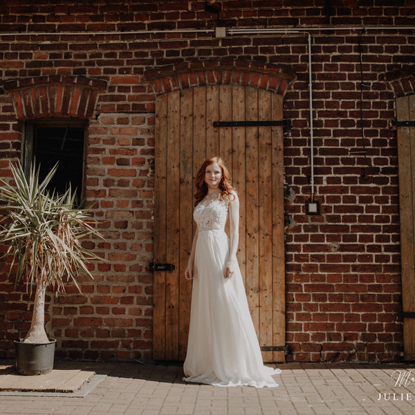 Braut steht vor Holztor