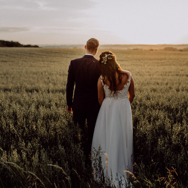 Brautpaar blickt über Kornfeld
