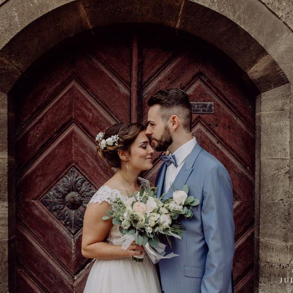Brautpaar küssend vor alter Kirche