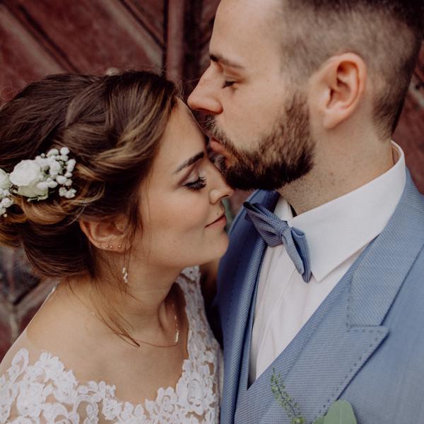 Brautpaar küssend vor alter Kirche nah