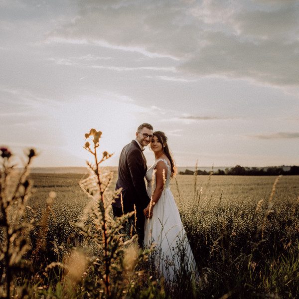 Brautpaar geht über Kornfeld