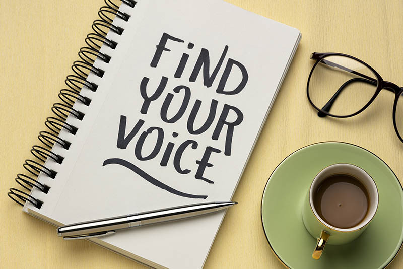 """""""Find Your Voice"""" written on a notebook next to coffee and glasses"""