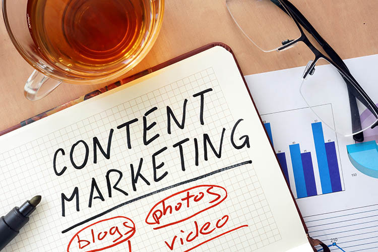 """""""Content Marketing"""" written on a notebook, next to some graphs, glasses, and a cup of tea"""
