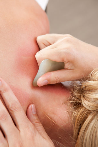 Female receiving gua sha treatment to neck and shoulders