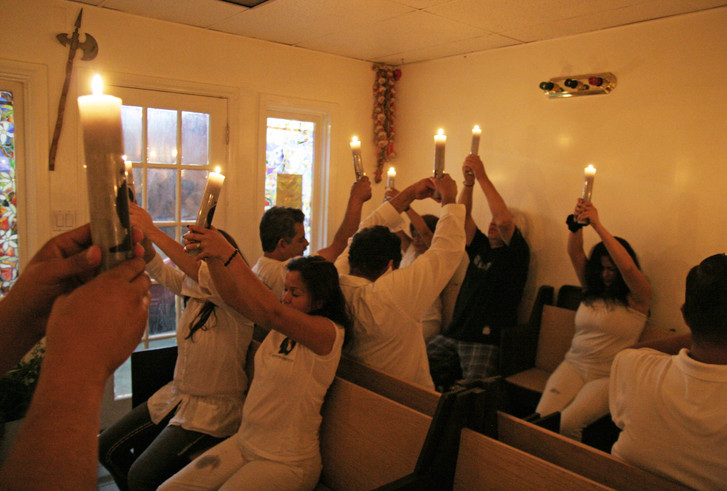 Worshipers at a Friday night Misa join in prayer to Jesus as well as Santa Muerte.
