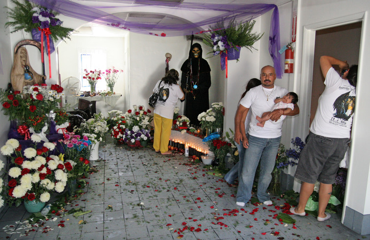 Sysiphus and Sahara have thrown a free three day event at the temple to commemorate the date of the first Santa Muerte temple's founding in Los Angeles. The floor is littered with rose petals and palm leaves from the morning's celebrations.