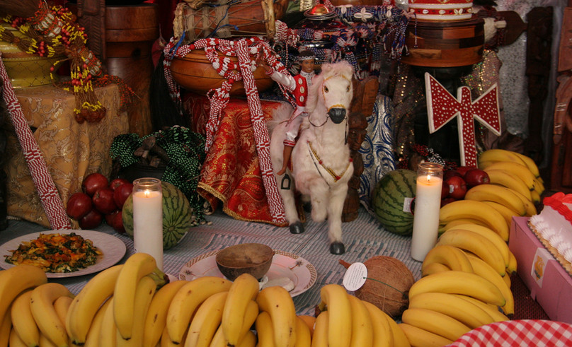 Shango, the Orisha of thunder and lighting, is depicted in literal form by the figure on horseback, and in symbolic form by the oshe (or double-headed axe), which represents swift and balanced justice. Today's celebration will consist of a ritual drumming for Shango, followed by an enormous feast during which the drummers eat first while the other guests wait respectfully. For the next week the throne will remain up to receive tribute from members of her religious family.