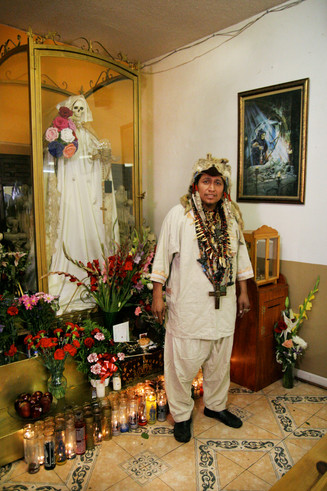 The Brujo Major (or Grand Shaman) hails from Veracruz, Mexico, and is the thirteenth generation in a long line of Mayan shamans. For him, Santa Muerte is a way to incorporate his indigenous beliefs while referencing the Catholic faith practiced by a large majority of Latinos.  His temple, Oracion de Santa Muerte, is located several blocks from MacArthur Park but attracts congregants from all over the city. Visitors pay their respects to the shrine with flowers, fruit, alcohol, candy, cigars, candles and money.
