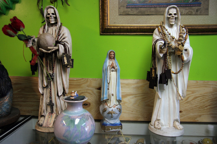 Although Santa Muerte is not sanctioned by the Catholic Church, many believers are also practicing Catholics, recognizing the Holy Trinity as superior to La Santissima. The actual origins of Santa Muerte are somewhat ambiguous, but the most common explanation is that she is a syncretism of The Virgin Mary and the Mesoamerican goddess Mictecacihuatl, to whom offerings would be made to insure a peaceful death and a place in the underworld for eternity.