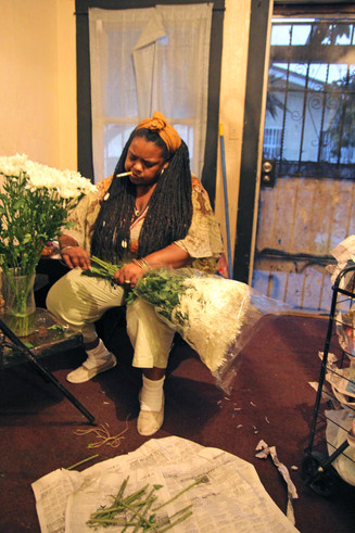 Orisaneke prepares for a Misa Blanca by preparing large bouquets of white carnations for the table, as tradition dictates.