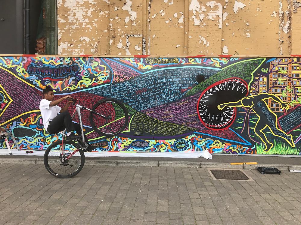 One Wheel Tye in front of Stop Loan Sharks mural on Ipswich Waterfront Photo: EVEWRIGHT