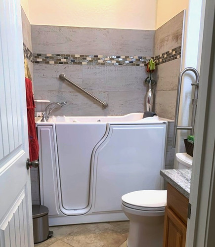 Walk-In Tub with grab bars and hand held shower head. Drop down grab bar at toilet