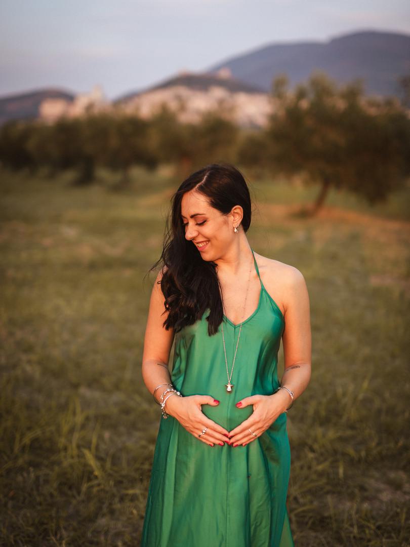 donna in gravidanza in un campo sotto assisi